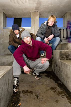 Three angry looking gangmembers in a dirty, concrete bunker at dusk.