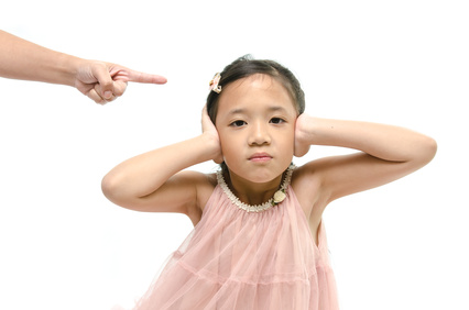 Little asian girl covering ears while mother scolding